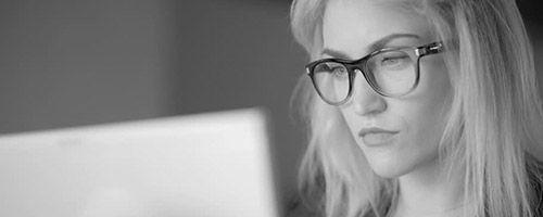 Blond kvinen foran laptop med briller