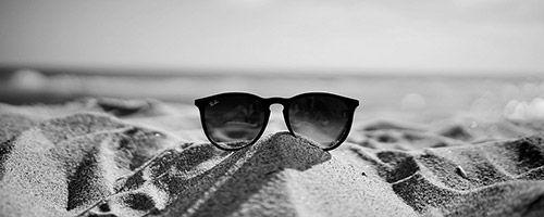 Solbriller i sanden på stranda